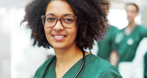 African American nurse in green scrubs.