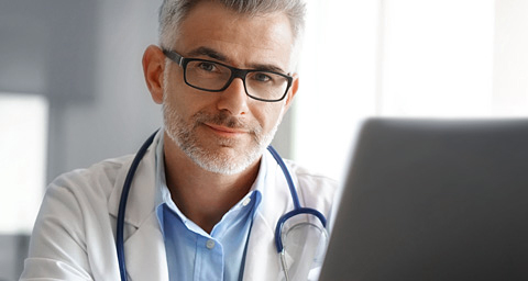 Mature doctor working at laptop.